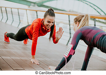 Women doing plank on riverside after running - Two young...