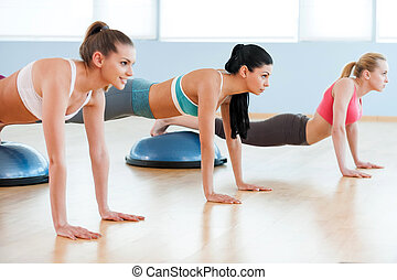 Women doing push-ups. Three beautiful young women in sports clothing doing push-up and smiling