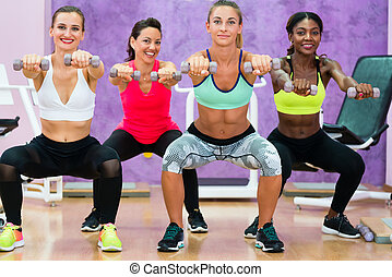 women doing squats holding dumbbells at functional training grou