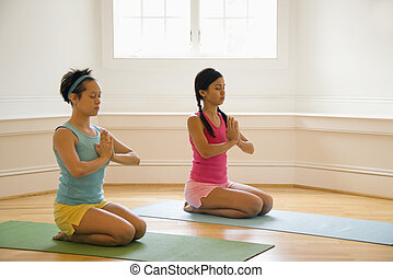 Women doing yoga - Two young women sitting on yoga mats with...