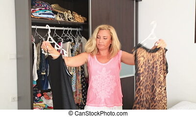 Women don't know what to wear - Woman chooses a dress