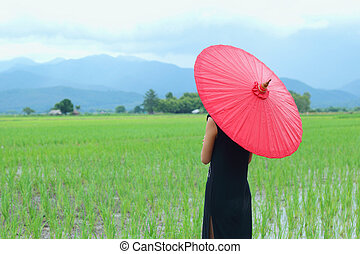 Women dressed in black with a red umbrella.