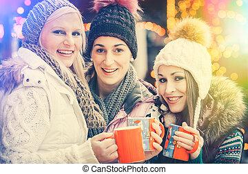 Women drinking mulled wine in mugs on German Christmas Market