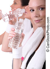 women drinking water after training