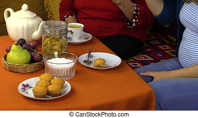 women eat sweets with tea