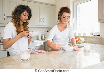 Women eating bowls of cereal in kitchen