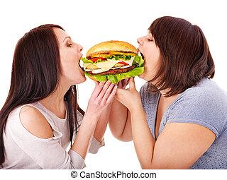 Women eating hamburger. Isolated.