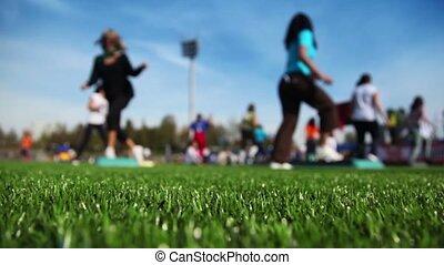 Women engaged in step aerobic on stadium