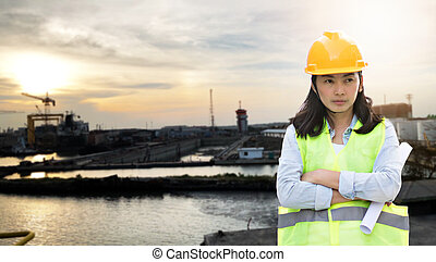 Women Engineering wearing hard hat and working at construction site