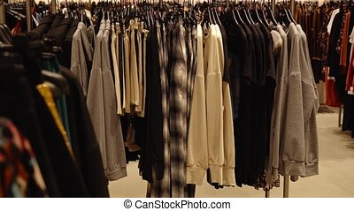 Large collection of new stylish women essential casual wear for everyday hanging on racks in empty contemporary fashion store