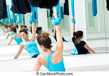 Women exercising bodies at aerial yoga class.