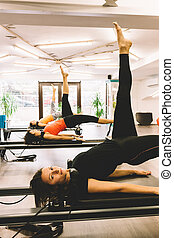 Women exercising in pilates room - Women stretching on ...