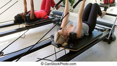 Women exercising on rowing machine 4k - Women exercising on...