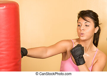Attractive young female working out on weight-lifting training machine