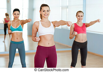 Women exercising. Three beautiful young women in sports clothing exercising and looking at camera