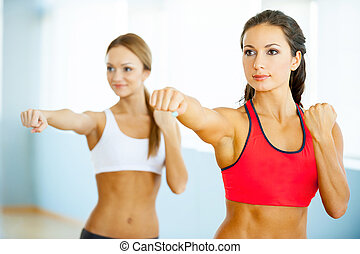 Women exercising. Two beautiful young women in sports clothing exercising and looking away