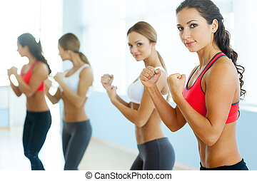 Women exercising. Two beautiful young women in sports clothing exercising and looking at camera