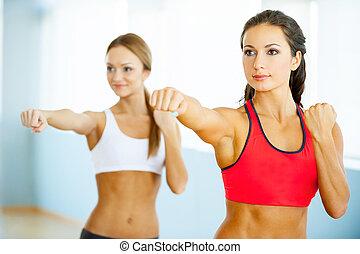 Women exercising. Two beautiful young women in sports ...