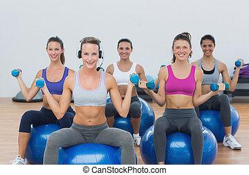 Women exercising with dumbbells on fitness balls