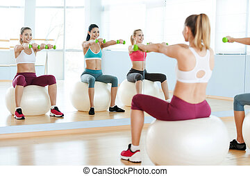 Women exercising with dumbbells. Three beautiful young women in sports clothing holding dumbbells and smiling at camera