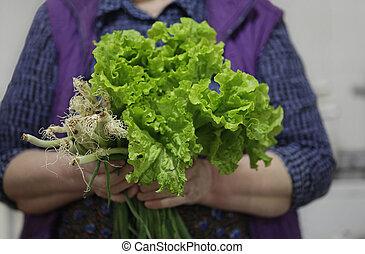 women farmer holding vegetables