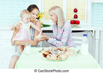 Women feed the child.