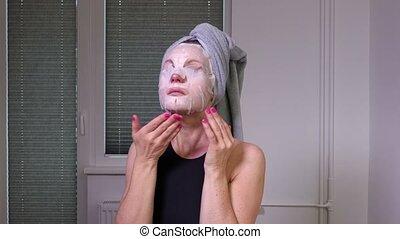 Women finish applying facial mask
