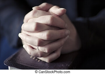 Women Folding Hands over a Bible