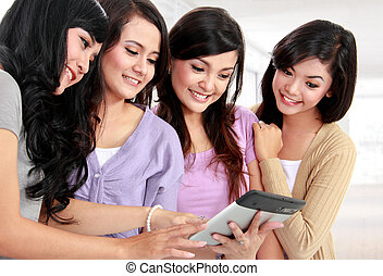 women friends at home using tablet computer