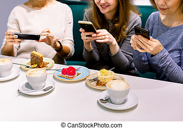 Women friends looking at cakes in cafe, making photos on the smartphones. Friends looking at photographs and laughing, cafe women, fun, enjoying