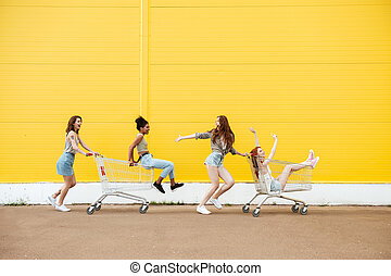 Women friends over yellow wall. Have fun with shopping trolley.