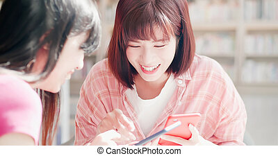 women friends using phone happily