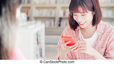 women friends using phone happily