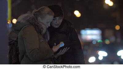 Women friends using tablet PC when waiting for bus in the street