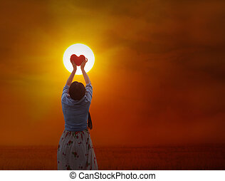 Back or rare view of women gently hold red heart with love, care and restpect to the sun on grass field and sunset twilight background