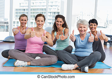 Women gesturing thumbs up in yoga class - Full length ...
