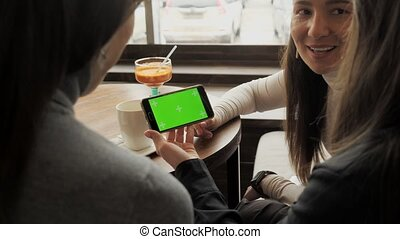 Women girlfriends are looking at green screen in smartphone...