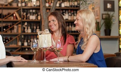 women giving present to friend at wine bar - people,...