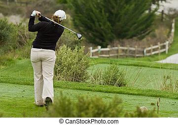 Women golfer swinging driver on tee box