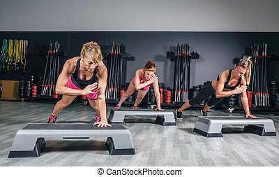 Women group training over steppers in aerobic class - Women...