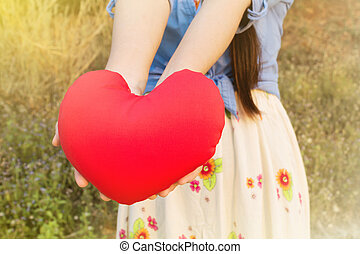 Women hand gently hold red heart with love, careness and restpect on wild grass flower field background