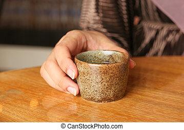 women hand holding a cup of green tea