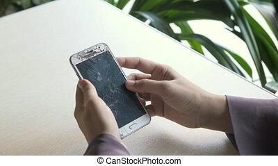 women hand holding broken smart phone