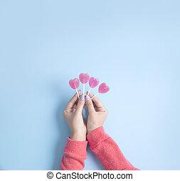 Women hand holding heart lollipop on blue background