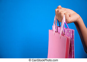 women hand holding shopping bag on blue background,