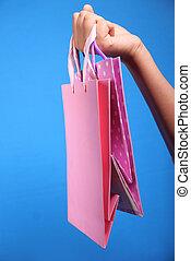 women hand holding shopping bag on blue background .