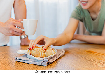 Women hand taking curry puff snacks with friend holding a coffee cup at home.