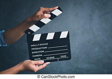 Women hands holding clapper board for making video cinema in studio.