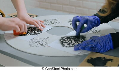 Women hands painting wooden circle - Stencil painting: women...