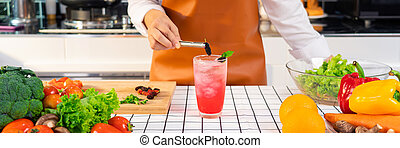 Women hands prepairing mocktail by putting sweet mulberry into a glass with an iced pink color drink.